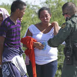 Skyrocketing numbers of immigrants such as these being questioned near McAllen have overburdened U.S. border security.