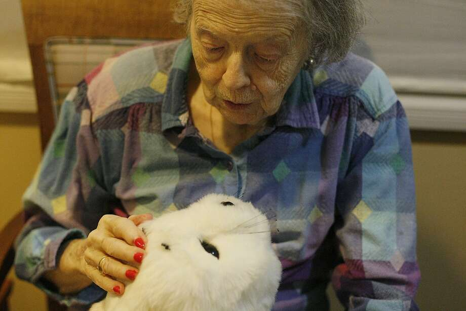 Joc Hartley plays with Paro the robotic seal at Sunny View Retirement Community in Cupertino, Calif. on Thursday, June 19, 2014. Robotic animals such as Paro are being used to help patients with memory loss as a form of therapy. Photo: James Tensuan, The Chronicle