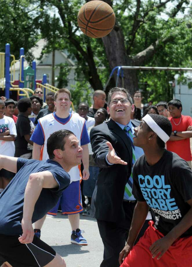 Larry Spring, Superintendent of Schenectady City School District, throws up the jump ball to begin play during an exhibition game between students, teachers and special guests Friday, June 20, 2014, at the King School in Schenectady, N.Y. The game was held in conjunction with a visit by professional women's basketball Player Julie McBride. (Michael P. Farrell/Times Union) Photo: Michael P. Farrell / 00027459A