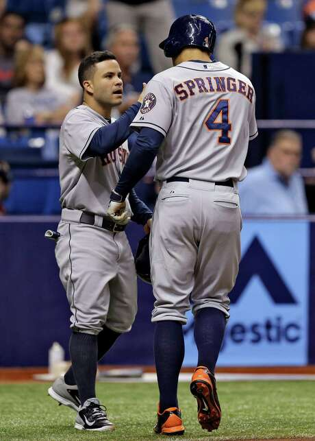 Jose Altuve, left, lets George Springer know how much he enjoyed watching the rookie's two-run homer in the third inning Friday night. Photo: Chris O'Meara, STF / AP