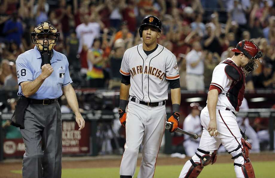 Home plate umpire Dan Iassogna calls San Francisco Giants' Ehire Adrianza out on strikes to end the baseball game,as Arizona Diamondbacks catcher Miguel Montero walks to the mound, Friday, June 20, 2014, in Phoenix. The Diamondbacks won 4-1.  (AP Photo/Matt York) Photo: Matt York, Associated Press