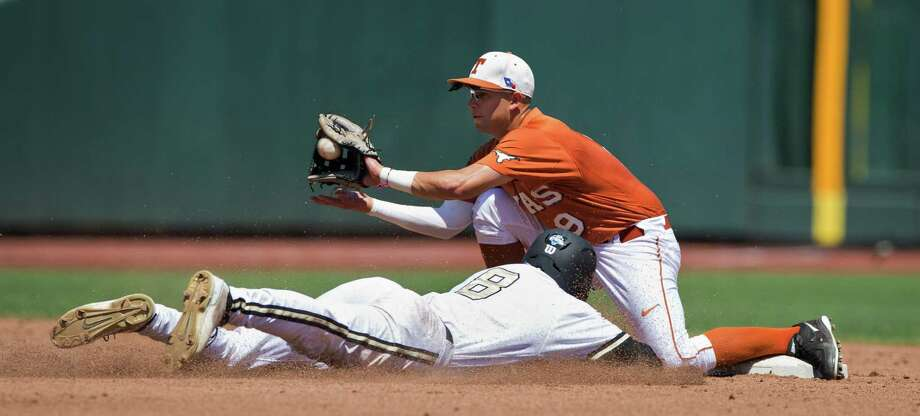 Vanderbilt's Rhett Wiseman (8) is tagged out trying to steal second base by Texas' C.J Hinojosa in the second inning of an NCAA baseball game in the College World Series in Omaha, Neb., on Friday, June 20, 2014. (AP Photo/Omaha World-Herald, Ryan Soderlin) Photo: Ryan Soderlin, Associated Press / Omaha World-Herald