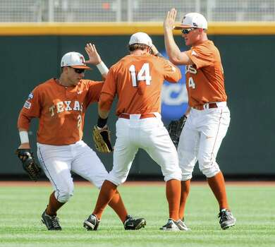 From left to right, Texas' Mark Payton, Ben Johnson and Collin Shaw celebrate after winning 4-0 against Vanderbilt in an NCAA baseball College World Series game in Omaha, Neb., Friday, June 20, 2014. (AP Photo/Eric Francis) Photo: Eric Francis, Associated Press / FR9944 AP