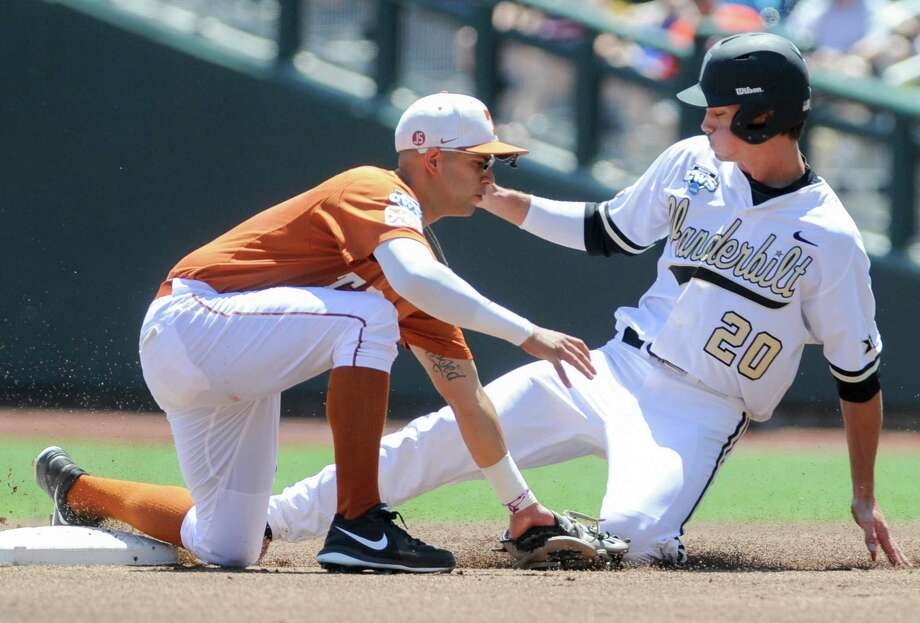 Vanderbilt left fielder Bryan Reynolds (20) reaches second base on a wild pitch against Texas shortstop C.J Hinojosa, left, in the first inning of an NCAA baseball College World Series game in Omaha, Neb., Friday, June 20, 2014. (AP Photo/Eric Francis) Photo: Eric Francis, Associated Press / FR9944 AP
