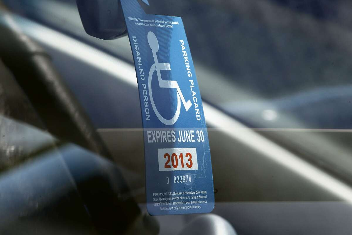A disabled parking placard is displayed in a parked vehicle along South Van Ness on Friday May, 17, 2013 in San Francisco, Calif. People with disabilities are having trouble finding parking in San Francisco making it more difficult to access their destinations. Current disabled parking placards and blue zone policies are failing to increase access for people with disabilities and reduce parking availability for all drivers. The City's Accessible Parking Policy Advisory Committee has worked together to present a better plan.