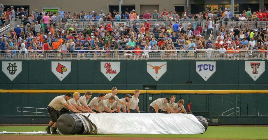 Grounds crew members roll the tarp onto the playing field during a rain delay in an NCAA baseball College World Series game between Mississippi and Virginia, in Omaha, Neb., Friday, June 20, 2014 (AP Photo/Ted Kirk) Photo: Ted Kirk, Associated Press / FR34398 AP