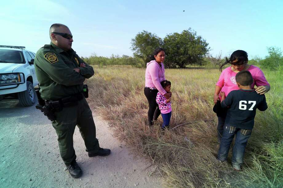 A U.S. Border Patrol agent with some of a group of 14 migrants from Honduras and Guatemala found near the Rio Grande River, near McAllen, Texas, June 18, 2014. The Obama administration, stepping up efforts to reduce the influx of Central American migrants crossing the border illegally, will detain more of them and accelerate their cases in immigration courts so they can be deported more quickly, officials said. (Jennifer Whitney/The New York Times) ORG XMIT: XNYT20 Photo: JENNIFER WHITNEY / © Jennifer Whitney