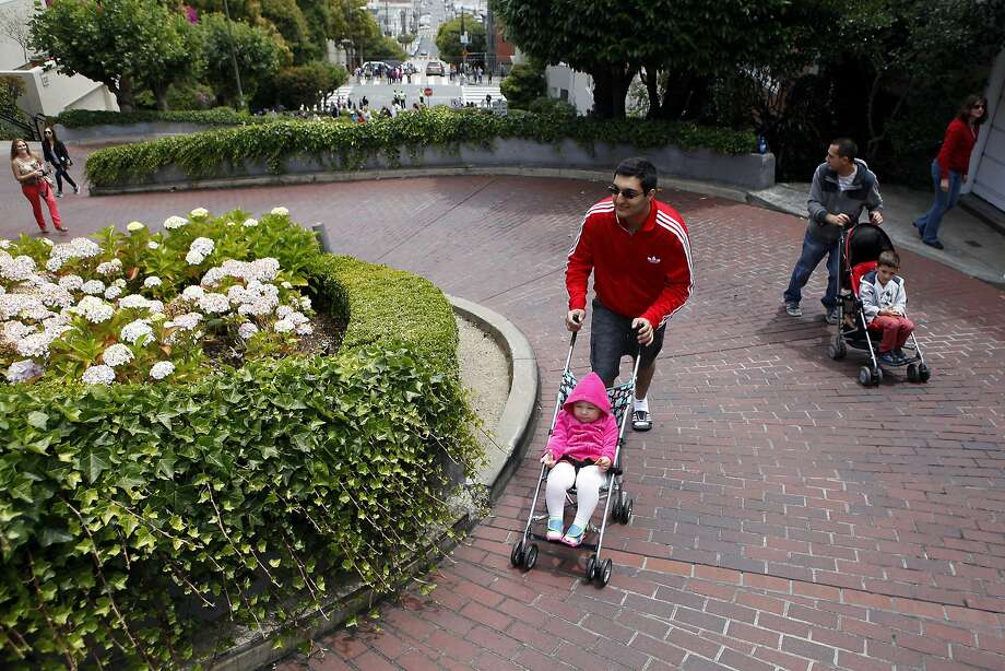 David Petrosyan pushes Carina Goul, 2, up Lombard Street as father Aram and brother Leo, 5, trail behind. The famously crooked S.F. street was closed to casual drivers Saturday for the first time under a new ban in effect for a few weekends. Photo: Michael Short, The Chronicle