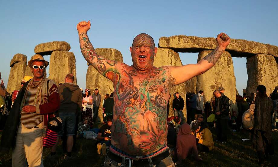 Mad Alan greets the longest day of the year:A well-illustrated reveler called Mad Alan (his real name, he says) celebrates the summer solstice with the rising of the sun at Stonehenge, near Amesbury, Englad. He was joined by modern druids and other pagan individuals at the prehistoric landmark. Photo: Geoff Caddick, AFP/Getty Images