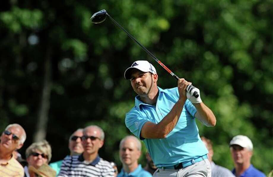 Sergio Garcia watches the flight of his ball during TravelersChampionship golf tournament in Cromwell, Conn., Saturday, June 21, 2014. Ryan Moore  leads with a three-day score of 13-under par. (AP Photo/Fred Beckham)