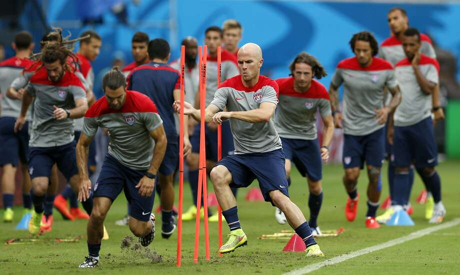 United States' Michael Bradley, center left, runs through obstacles with teammates during a training session at the Arena da Amazonia in Manaus, Brazil, Sunday, June 22, 2014. The U.S. will play Portugal in group G of the 2014 soccer World Cup on June 22. (AP Photo/Paulo Duarte) Photo: Julio Cortez, Associated Press
