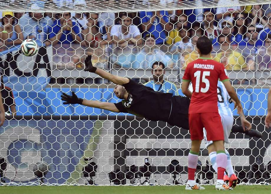 Iran goalkeeper Alireza Haghighi dives but fails to stop a goal by Argentina's Lionel Messi in extra time of a key Group F match in Belo Horizonte, Brazil. Photo: Martin Meissner, Associated Press