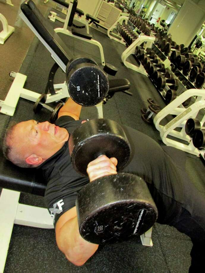 Gunney DominguezâÄôs workout includes an easy press with these 95 pound weights. Photo: Anne W. Semmes / Greenwich Time