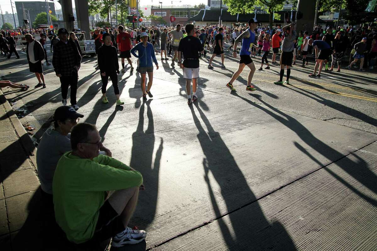 Some runners sit while others warm up prior to the event.