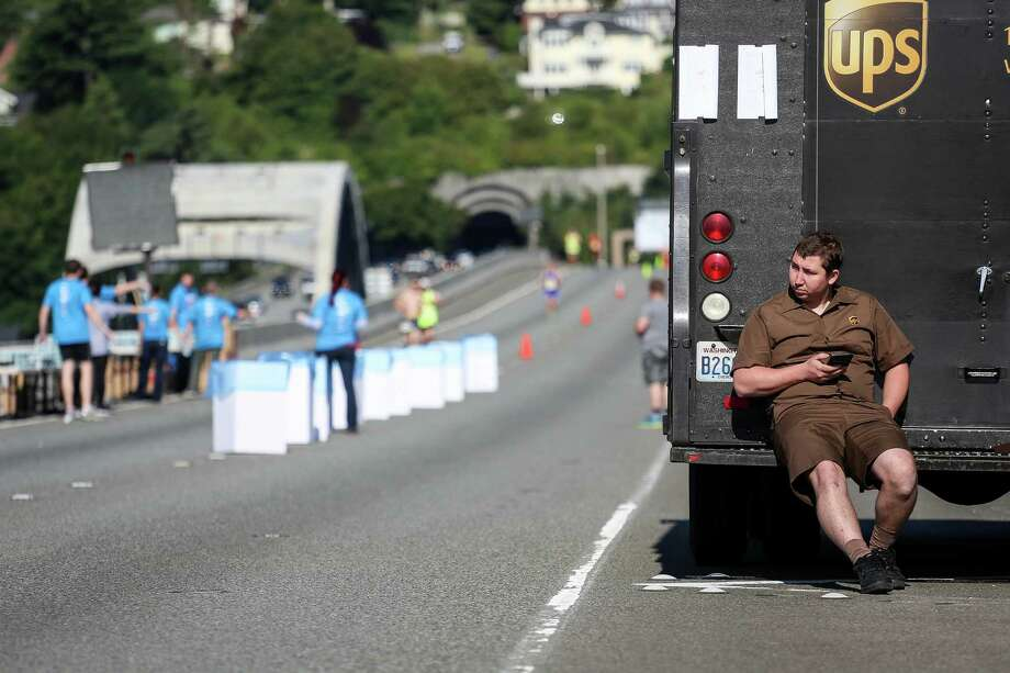 A stranded UPS driver watches runners cross the Interstate 90 floating bridge. Photo: JOSHUA BESSEX, SEATTLEPI.COM / SEATTLEPI.COM