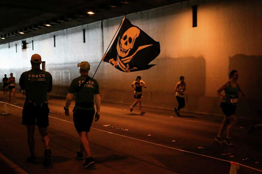 Trainers walk with the Jolly Roger while runners make their way through the Interstate 90 tunnel. Photo: JOSHUA BESSEX, SEATTLEPI.COM / SEATTLEPI.COM