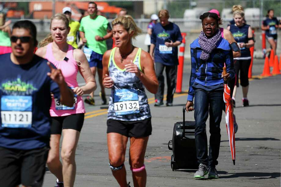 A woman with a rolling suitcase walks alongside runners. Photo: JOSHUA BESSEX, SEATTLEPI.COM / SEATTLEPI.COM