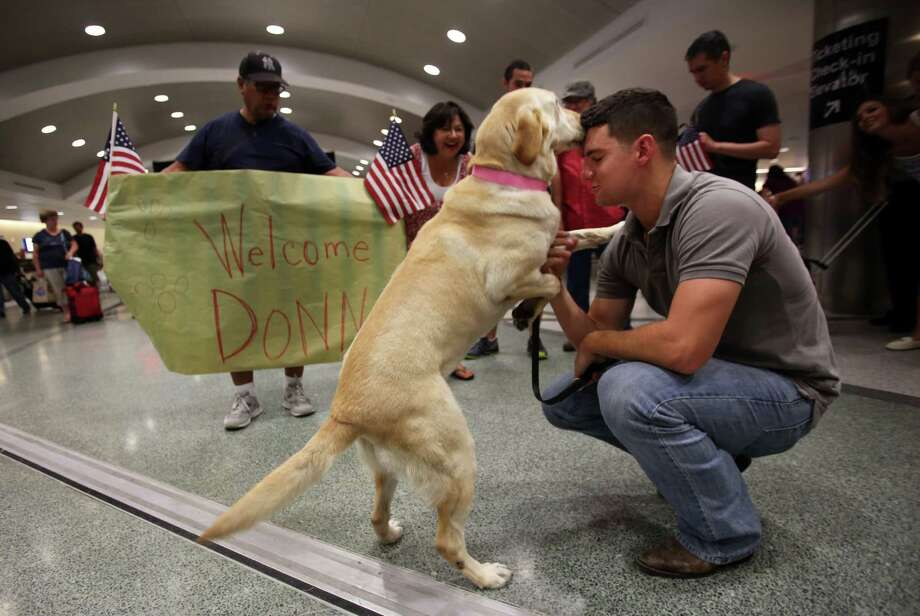 Marine Corp. Cpl. Joaquin Aranda, is reunited with his military war dog, Donna, at Houston Hobby Airport on Saturday. Donna swept for bombs with Aranda in Afghanistan. Photo: Mayra Beltran, Staff / © 2014 Houston Chronicle