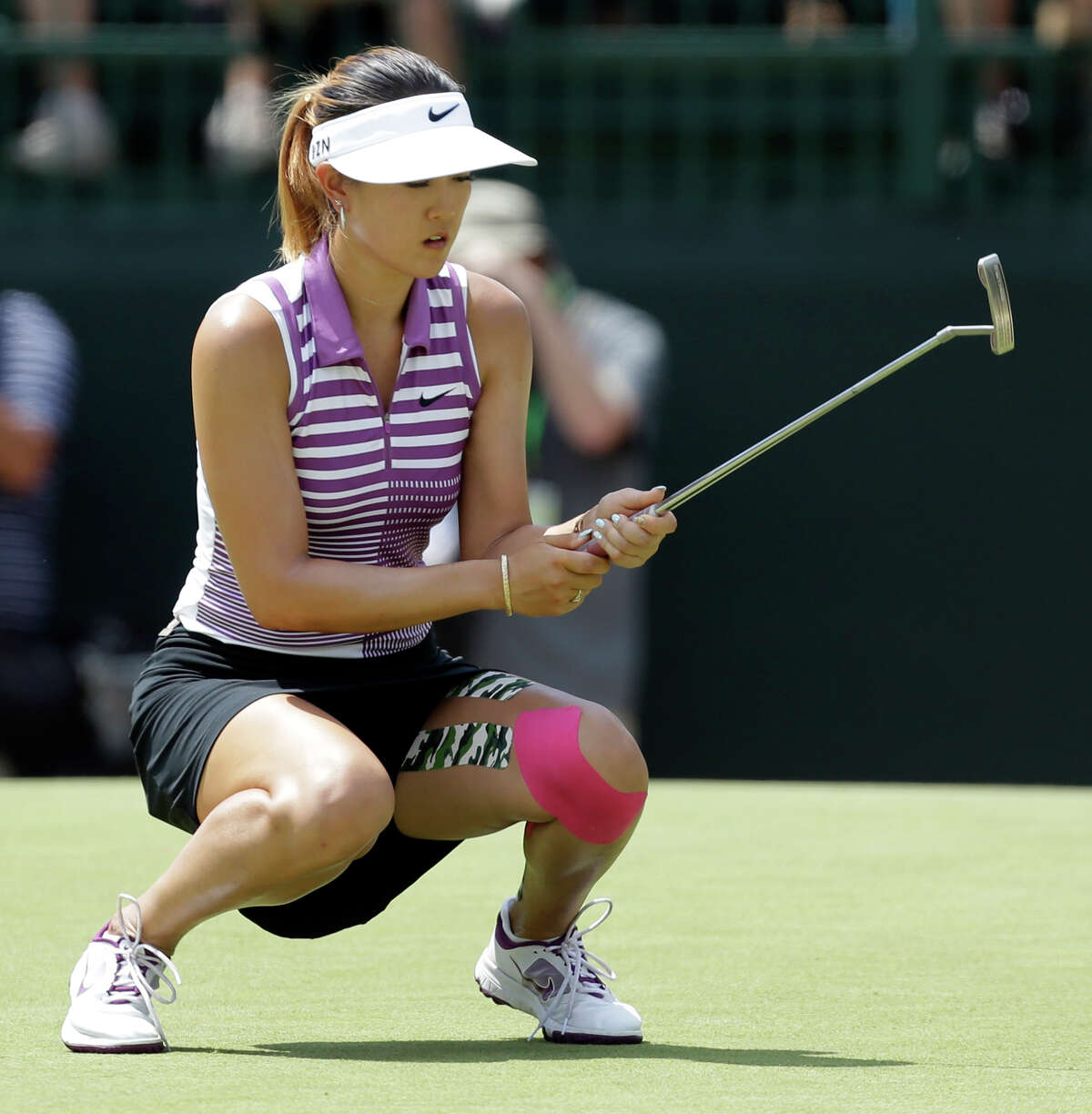Michelle Wie reacts after missing a putt on the fifth hole during the third round of the U.S. Women's Open golf tournament in Pinehurst, N.C., Saturday, June 21, 2014. (AP Photo/Bob Leverone) ORG XMIT: NCCB123