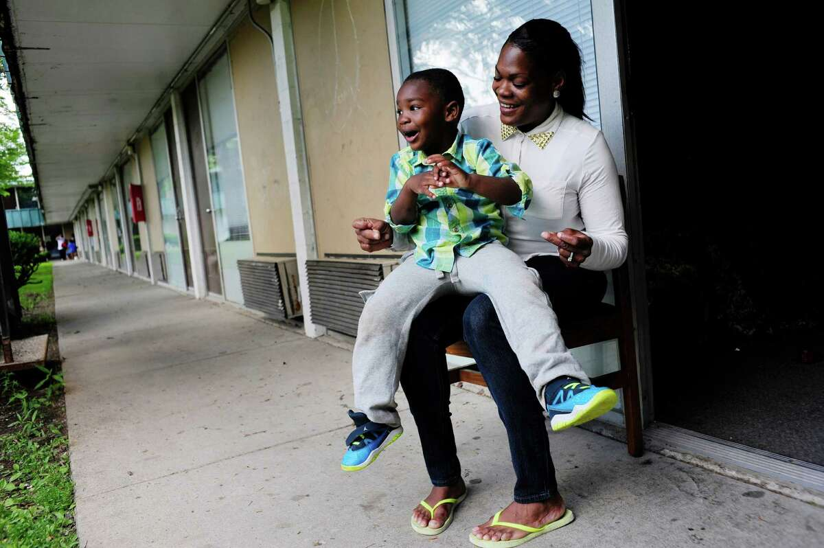 Tonya Sykes and her son Nehemiah O'Sullivan, 3, sing as they sit outside one of their rooms at the Schuyler Inn on Thursday, June 19, 2014, in Menands, N.Y. Sykes and her children are living at inn after running into problems with their Albany apartment. (Paul Buckowski / Times Union)