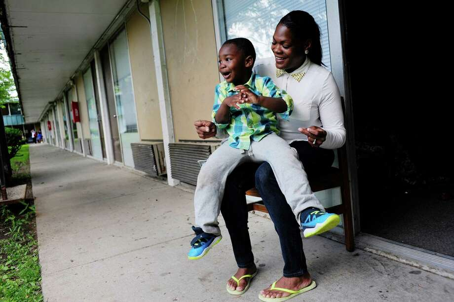 Tonya Sykes and her son Nehemiah O'Sullivan, 3, sing as they sit outside one of their rooms at the Schuyler Inn on Thursday, June 19, 2014, in Menands, N.Y.  Sykes and her children are living at inn after running into problems with their Albany apartment.   (Paul Buckowski / Times Union) Photo: Paul Buckowski / 00026452A
