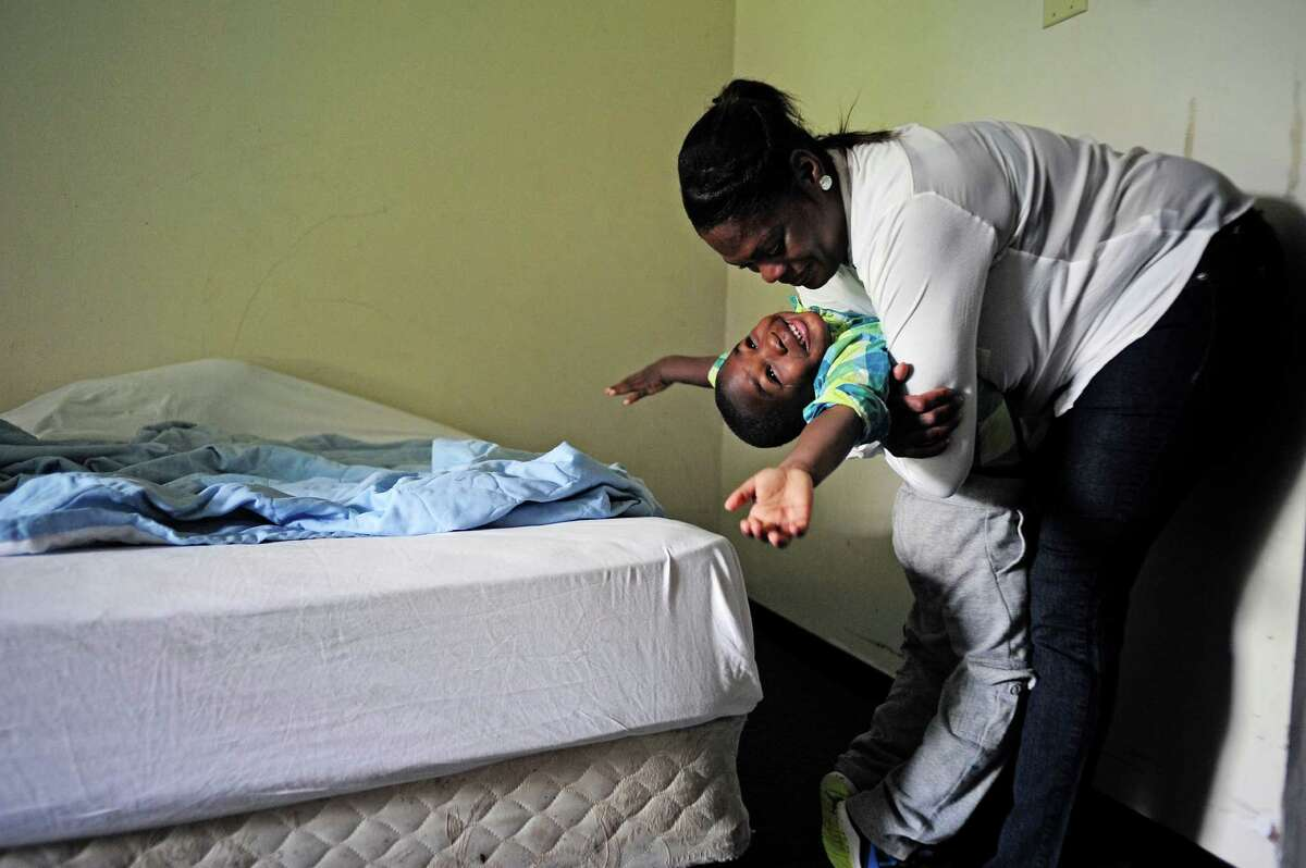 Tonya Sykes gives a hug to her son Nehemiah O'Sullivan, 3, in one of their rooms at the Schuyler Inn on Thursday, June 19, 2014, in Menands, N.Y. Sykes stopped working after different crisis befell her children, and lost her apartment after it flooded. (Paul Buckowski / Times Union)