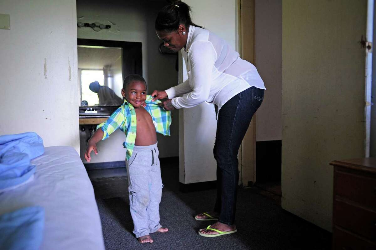 Tonya Sykes helps her son Nehemiah O'Sullivan, 3, get dressed in one of their rooms at the Schuyler Inn on Thursday, June 19, 2014, in Menands, N.Y. Sykes' four children are among the hundreds that are classified as homeless in the City of Albany. (Paul Buckowski / Times Union)
