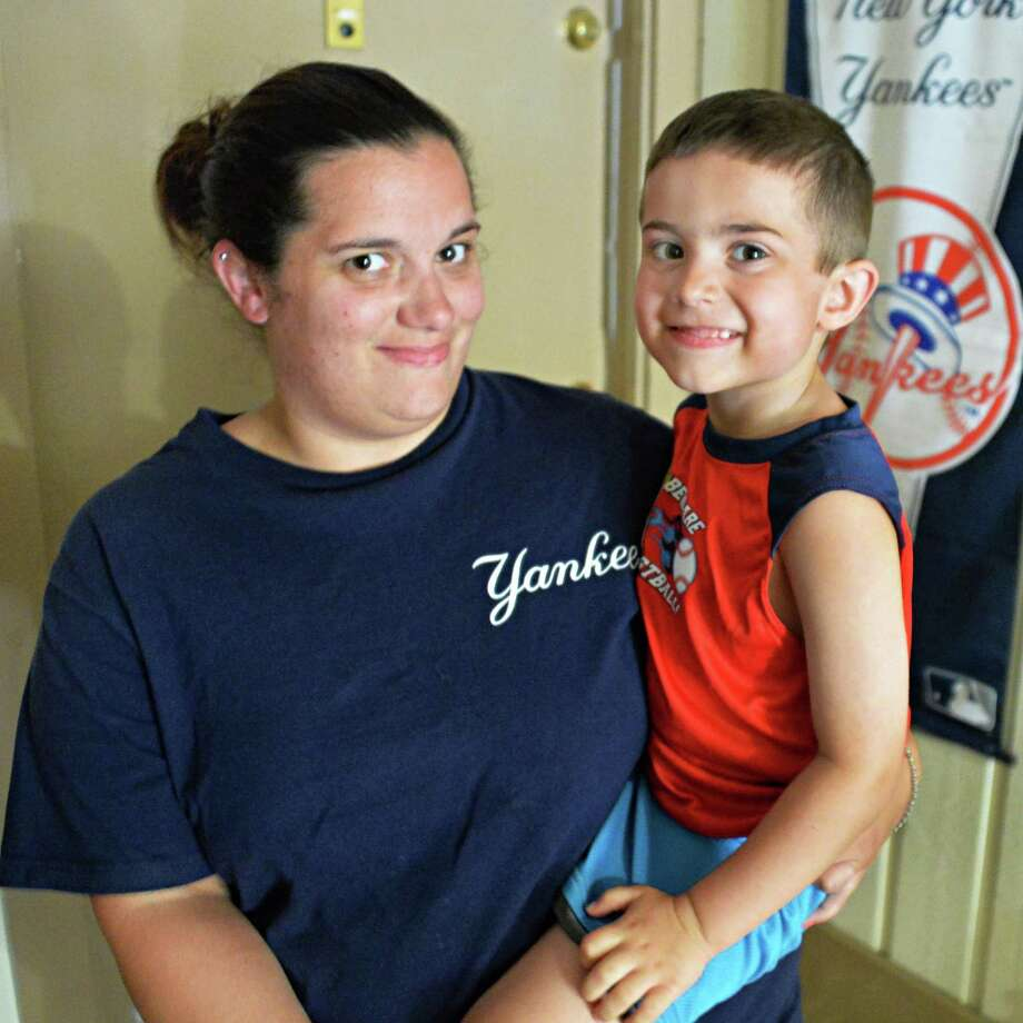 Jessica DeZalia holds her 4-year-old son Trystan DeZalia in front of their Fox Run apartment Saturday June 21, 2014, in Clifton Park, NY. It was Trystan that heard a neighbor's smoke alarm and alerted family members of an early morning fire in their apartment complex.  (John Carl D'Annibale / Times Union) Photo: John Carl D'Annibale