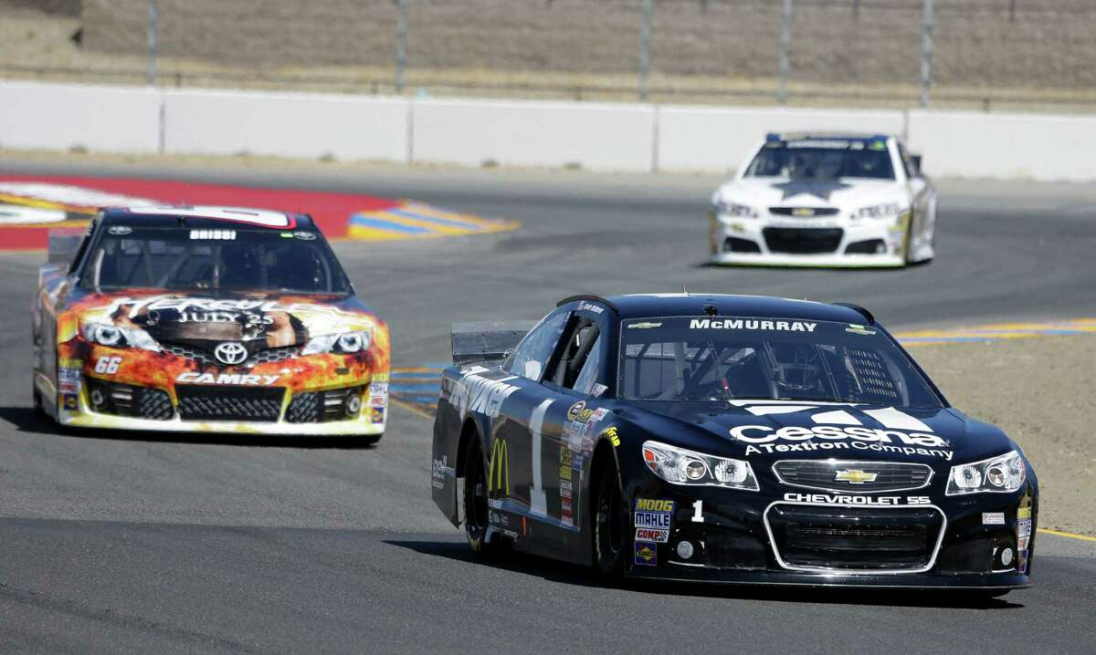 Jamie McMurray leads Tomy Drissi, left, and Dale Earnhardt Jr., top right, during qualifying for the NASCAR Sprint Cup series auto race Saturday, June 21, 2014, in Sonoma, Calif. McMurray was the pole winner. (AP Photo/Eric Risberg) ORG XMIT: CAER101