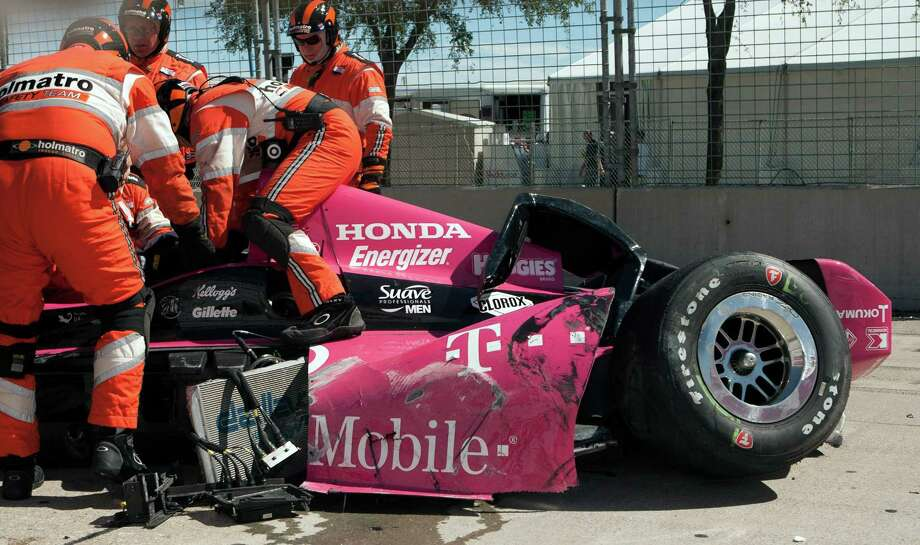 Safety team members work to remove driver Dario Franchitti from his car after his crash during the second IndyCar Grand Prix of Houston last October. The crash underscored the need for safety improvements.  Photo: Juan DeLeon, FRE / AP