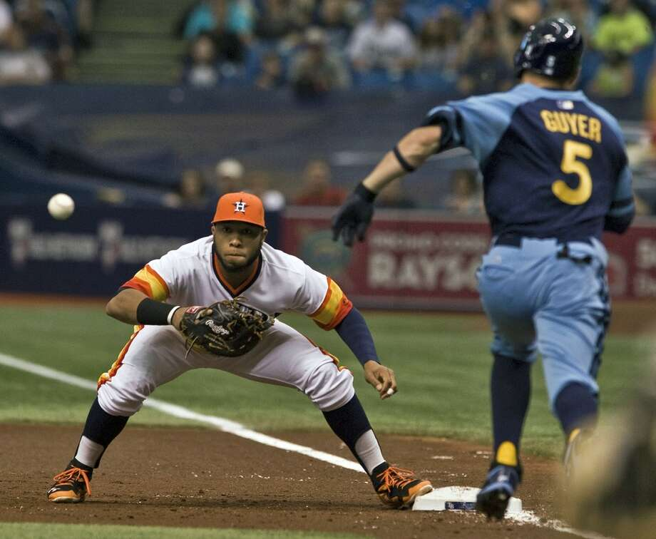 Jon Singleton, left, reaches for the throw from pitcher Jake Buchanan to force out Rays' Brandon Guyer during the first inning. Photo: Steve Nesius, Associated Press