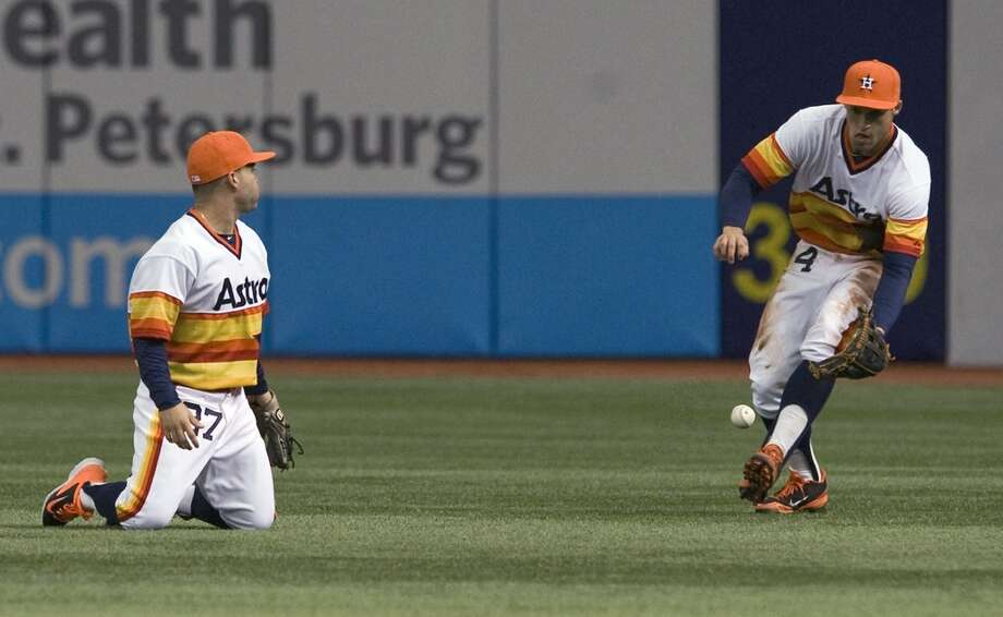 Astros second baseman Jose Altuve, left, looks on as right fielder George Springer (4) fields an RBI bloop-single hit by Rays' Evan Longoria during the first inning. Photo: Steve Nesius, Associated Press
