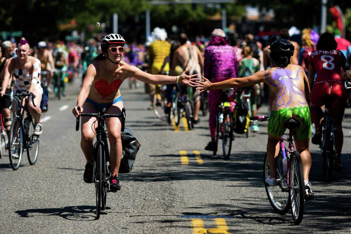 Nude bicyclists trade high fives from their bike seats at the 26th annual Fremont Solstice Parade on Saturday, June 21, 2014, in Seattle. The parade, as part of the Fremont Fair, ended in Gas Works Park with HONK! Fest West, where the celebration with local and national street bands, food, beverages and art carried on until nightfall.