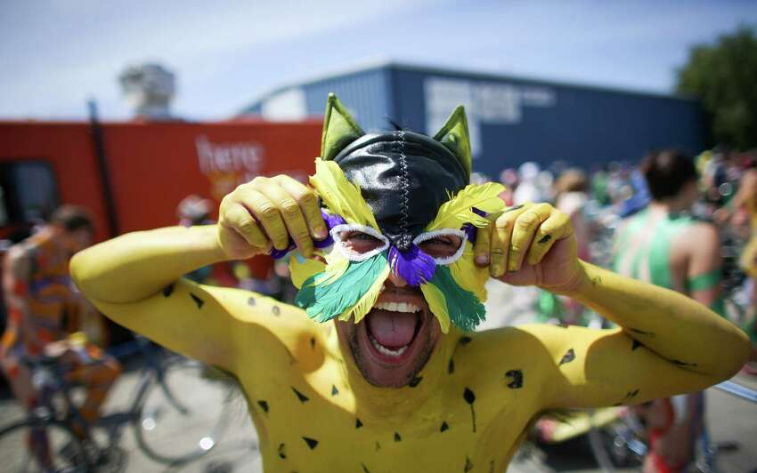 A painted cyclist adjusts his mask during the annual Fremont Solstice Parade.