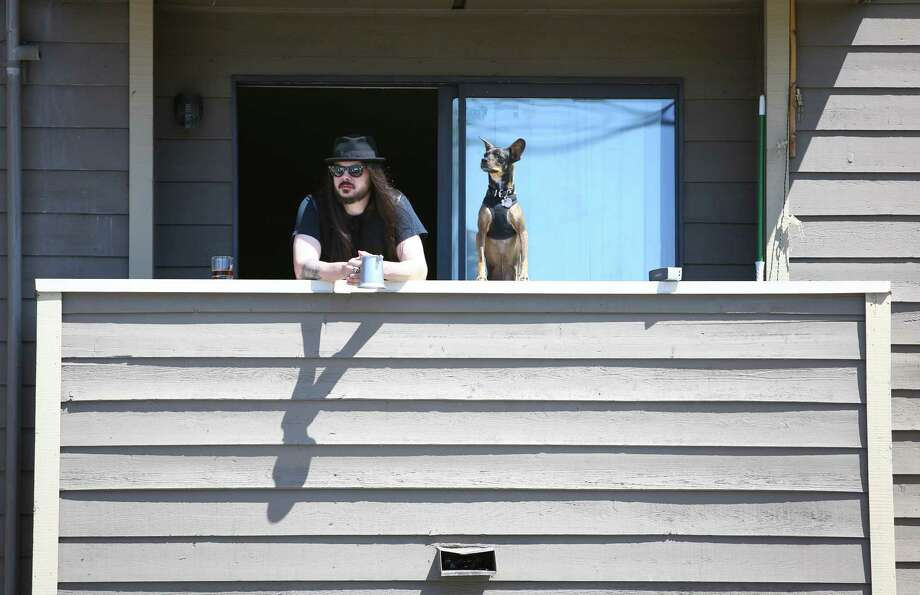 A spectator watches the action from an apartment balcony. Photo: JOSHUA TRUJILLO, SEATTLEPI.COM / SEATTLEPI.COM