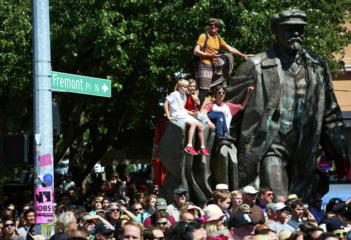 Spectators watch from Fremont's Lenin statue during the annual Fremont Solstice Parade on Saturday, June 21, 2014.