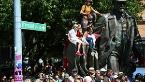 Spectators watch from Fremont's Lenin statue during the annual Fremont Solstice Parade. The 2014 edition of the parade featured cloud free skies on the first day of summer. Photographed on Saturday, June 21, 2014.