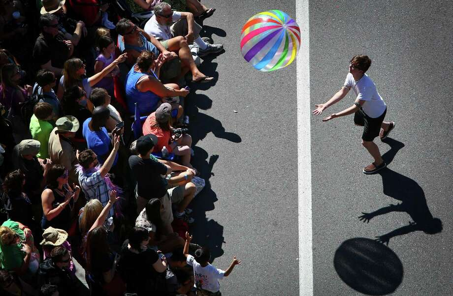 A parade participant tosses a ball to the crowd. Photo: JOSHUA TRUJILLO, SEATTLEPI.COM / SEATTLEPI.COM