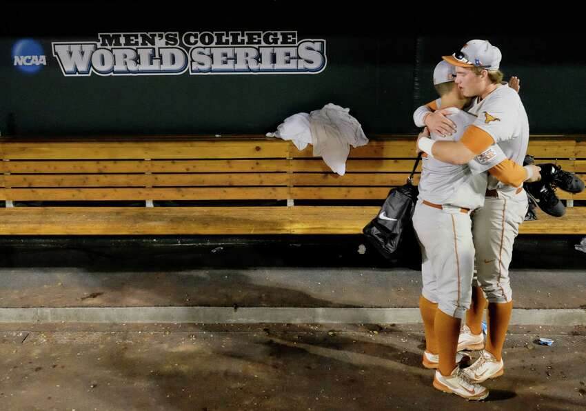 Texas' Mark Payton, left, and Kacy Clemens, right, hug in the dugout after Texas lost 4-3 to Vanderbilt in 10 innings in an NCAA baseball College World Series elimination game in Omaha, Neb., Saturday, June 21, 2014. Vanderbilt advanced to the championship series. (AP Photo/Eric Francis)