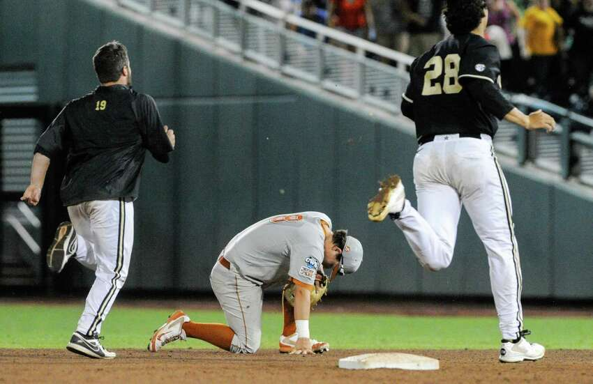 Texas second baseman Brooks Marlow, center, crouches near second base as Vanderbilt's Steven Rice (19) and Jared Miller (28) run to celebrate Vanderbilt's 4-3 to win over Texas in 10 innings in an NCAA baseball College World Series elimination game in Omaha, Neb., Saturday, June 21, 2014. Vanderbilt advanced to the championship series. (AP Photo/Eric Francis)