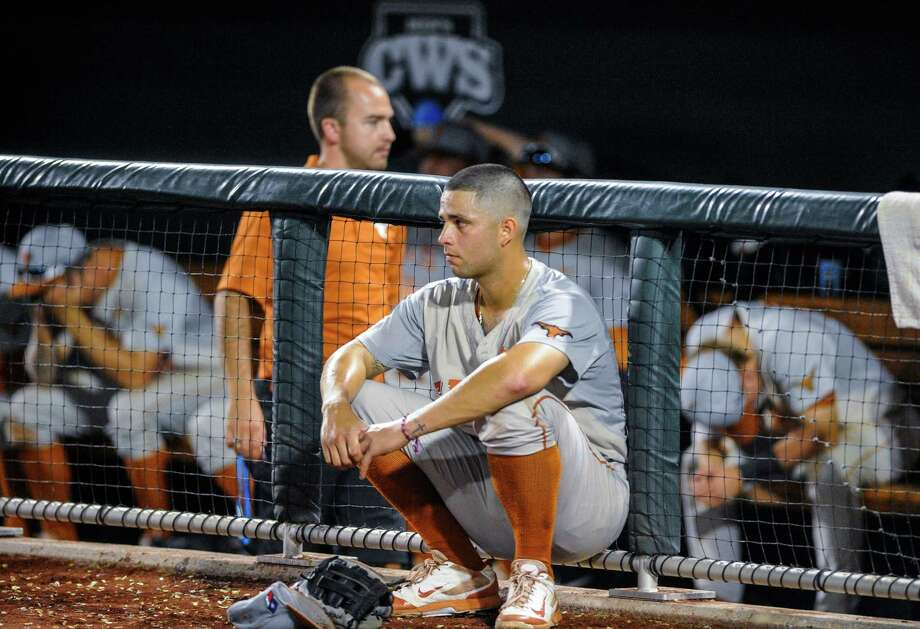 Texas shortstop C.J Hinojosa sits outside the dugout after Texas lost 4-3 to Vanderbilt in 10 innings in an NCAA baseball College World Series elimination game in Omaha, Neb., Saturday, June 21, 2014. Vanderbilt advanced to the championship series. (AP Photo/Eric Francis) Photo: Eric Francis, Associated Press / FR9944 AP