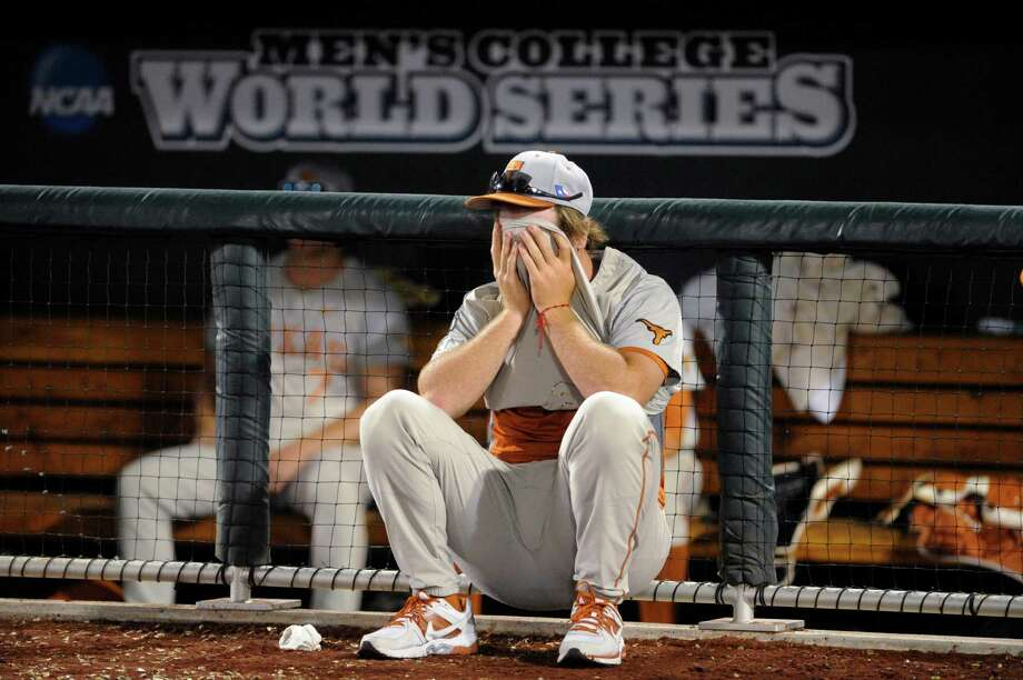 Texas pitcher Dillon Peters covers his face in frontof  the dugout after Texas lost 4-3 to Vanderbilt in 10 innings in an NCAA baseball College World Series elimination game in Omaha, Neb., Saturday, June 21, 2014. Vanderbilt advanced to the championship series. (AP Photo/Eric Francis) Photo: Eric Francis, Associated Press / FR9944 AP