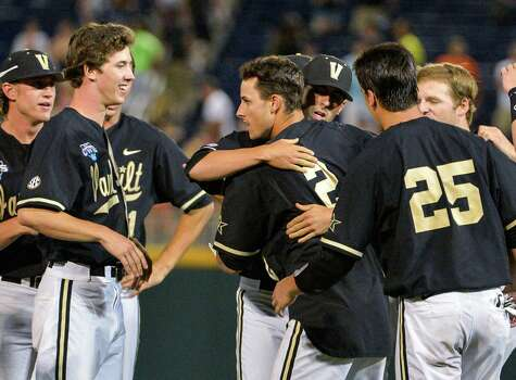 Vanderbilt players surround Tyler Campbell (2) who hit a single in the 10th inning that scored Rhett Wiseman for a 4-3 win over Texas in an NCAA baseball College World Series game in Omaha, Neb., Saturday, June 21, 2014. Vanderbilt advanced to the championship series. (AP Photo/Ted Kirk) Photo: Ted Kirk, Associated Press / FR34398 AP