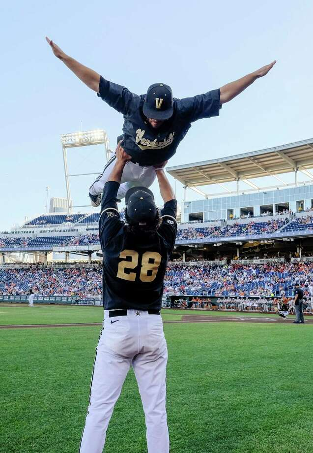 Vanderbilt pitcher Jared Miller (28) hoists teammate Steven Rice as part of team ritual, before an NCAA baseball College World Series game against Texas in Omaha, Neb., Saturday, June 21, 2014. (AP Photo/Eric Francis) Photo: Eric Francis, Associated Press / FR9944 AP