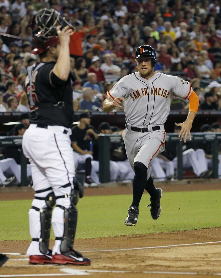Arizona Diamondbacks catcher Miguel Montero, left, waits for the throw as San Francisco Giants' Hunter Pence scores on an RBI-single by Pablo Sandoval during the first inning of a baseball game on Saturday, June 21, 2014, in Phoenix. (AP Photo/Matt York) Photo: Matt York, Associated Press