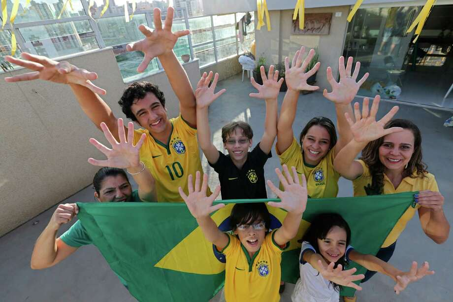 Members of the Silva family, back row, from left, Silvia Santos, Joao de Assis, Pedro de Assis, Ana Carolina Santos and Silvana Santos, front row, Bernardo de Assis, left, and Maria Morena Santos, pose for a photo in their home to show that they each have six fingers on each of their hands, in Brasilia, Brazil, Thursday, June 19, 2014. The family was born with an extra digit on each hand as a result of a genetic condition known as polydactyly. Photo: Eraldo Peres, AP  / AP2014