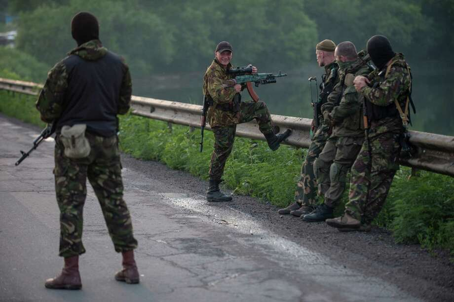 A pro-Russian fighter holds a gun during a handover of the bodies of Ukrainian troops killed in the plane shot down near Luhansk, at a check point in the village of Karlivka near Donetsk, eastern Ukraine, Wednesday, June 18, 2014. The two sides managed to arrange a brief truce Wednesday evening in the eastern town of Karlivka to allow pro-Russian forces to hand over the bodies of 49 Ukrainian troops who died when the separatists shot down a transport plane bound for the airport in Luhansk last weekend. Photo: Evgeniy Maloletka, AP  / AP2014