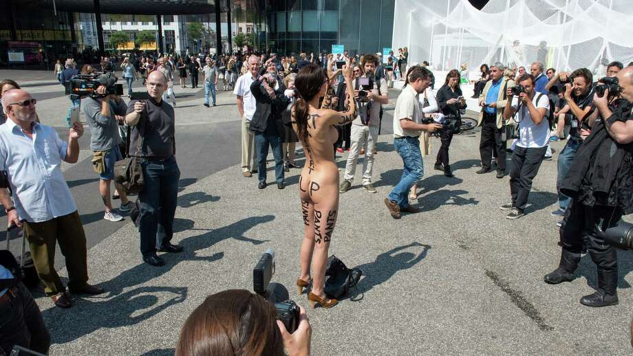 "Swiss performance artist Milo Moire walks naked on the exhibition site of the international art show Art Basel and takes pictures, in Basel, Switzerland, on Thursday, June 19, 2014. Controversial Swiss artist Milo Moire names her performance of her walk naked through the Art Basel exhibition ""The Script System"". Photo: Georgios Kefalas, AP  / AP"