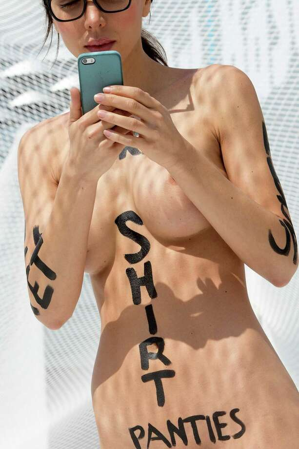 "Swiss performance artist Milo Moire holds a smart phone as she walks naked on the exhibition site of the international art show Art Basel and takes pictures, in Basel, Switzerland, on Thursday, June 19, 2014. Controversial Swiss artist Milo Moire names her performance of her walk naked through the Art Basel exhibition ""The Script System"". Photo: Georgios Kefalas, AP  / AP2014"