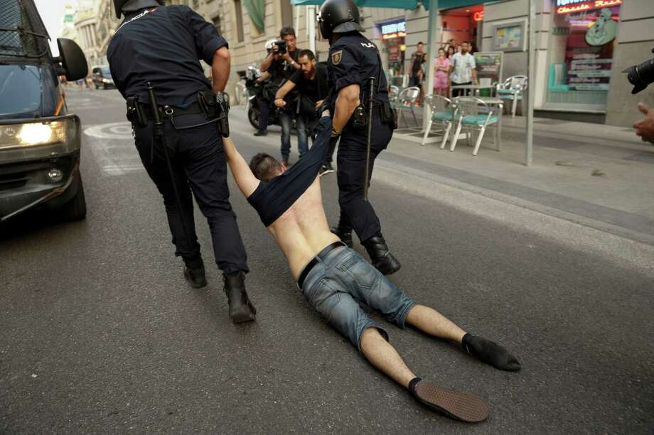 A Republican demonstrator is detained by riot police officers after trying to protest against the monarchy in the center of Madrid, Spain, on Thursday, June 19, 2014. Dozens of protestors gathered in Madrid's main square to protest against the Spanish Monarchy on the day Spain's King Felipe VI was crowned. Felipe is being formally proclaimed monarch Thursday after 76-year-old King Juan Carlos abdicated so that younger royal blood can rally a country beset by economic problems, including an unemployment rate of over 25 percent. Photo: Daniel Ochoa De Olza, AP  / AP2014